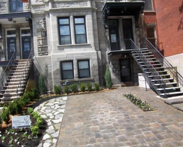 """Stationnement et terrasse avant en pavé-uni et """"flagstone"""" - aménagement avec jardin en facade."""